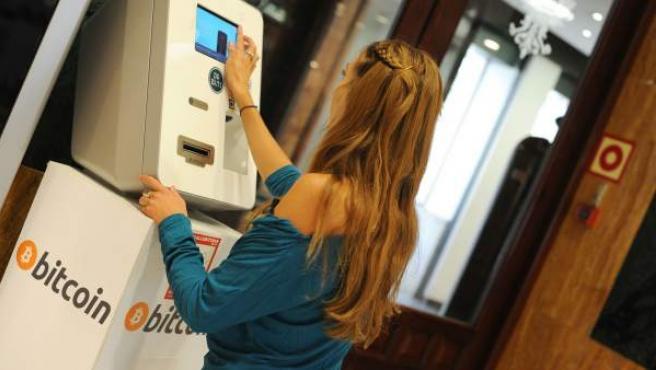 Una joven una un cajero de bitcoin en Madrid.