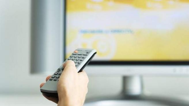 Una persona apunta con el mando a distancia a la televisión.