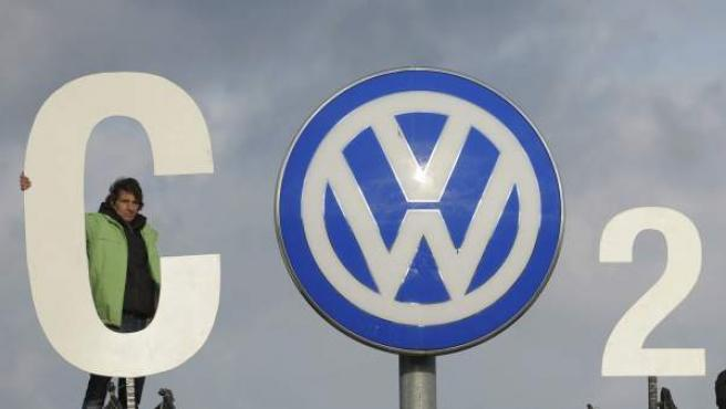 Un activista de Greenpeace protesta junto al logotipo de Volkswagen en la fábrica de Wolfsburgo (Alemania).