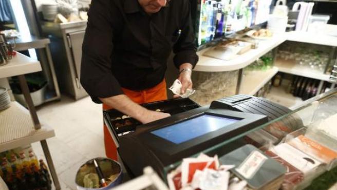 Un camarero abriendo la caja registradora para cobrar a un cliente.