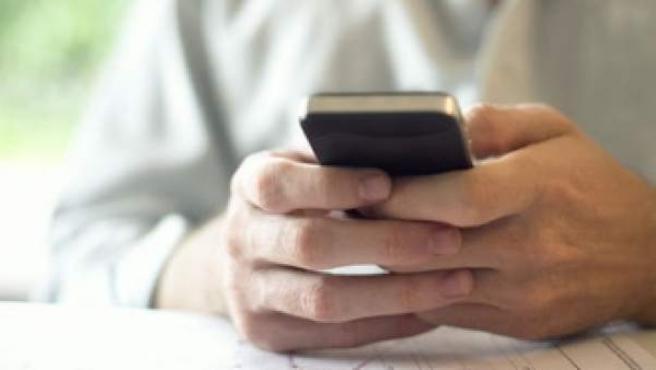 Un hombre con su teléfono móvil.