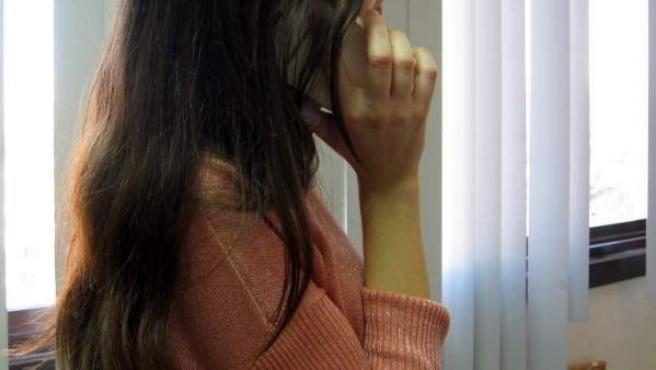 Una joven habla por el móvil.