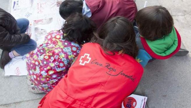 Una voluntaria de Cruz Roja junto a niños