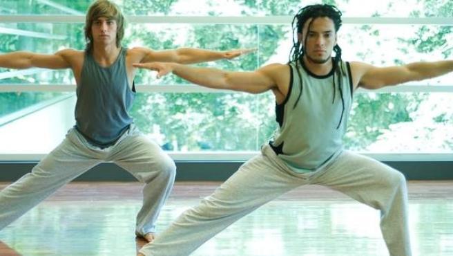 Dos hombres jóvenes ejercitándose en pilates.