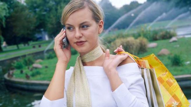 Una mujer realiza compras mientras habla por el teléfono
