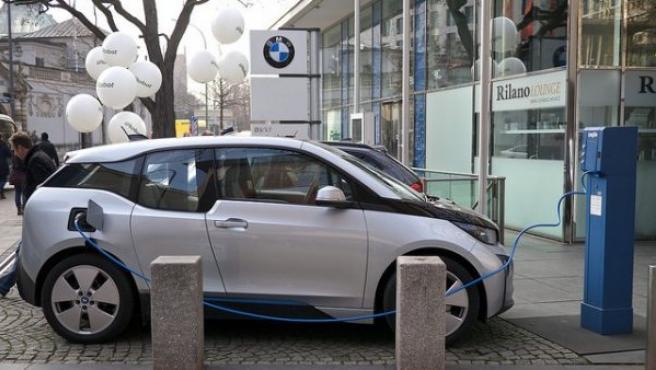 Un BMW i3 carga sus baterías en un punto de recarga habilitado en la calle.