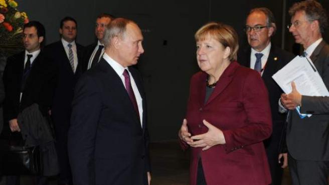 El presidente de Rusia Vladimir Putin (c-i) habla con la canciller alemana Angela Merkel.