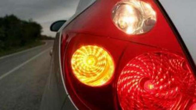 Un coche con el intermitente encendido señaliza un desplazamiento lateral.