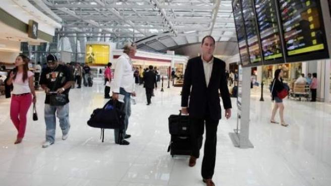 Un pasajero con su maleta en un aeropuerto.