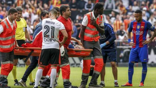 El centrocampista del FC Barcelona Andrés Iniesta es retirado en camilla del campo tras sufrir una lesión durante el partido frente al Valencia CF.