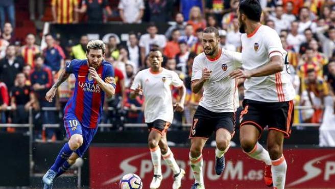 El jugador del FC Barcelona Leo Messi (i) conduce el balón, ante el mediocentro del Valencia Mario Suárez (2d) y el defensa valencianista Ezequiel Garay (d).