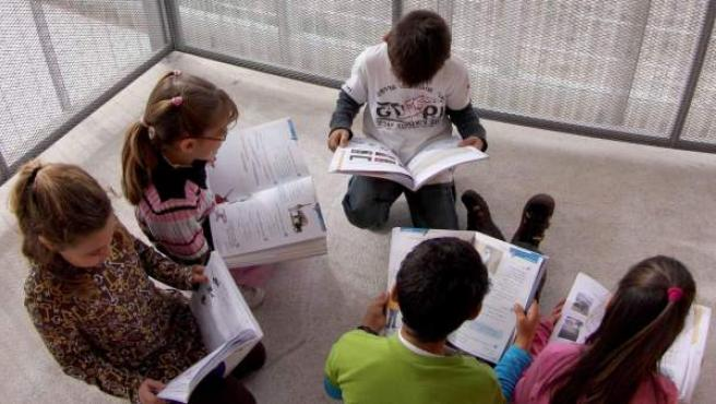 Varios alumnos leen sus libros de texto.