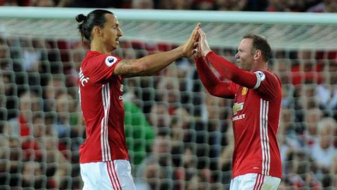 Zlatan Ibrahimovic (i) celebra un tanto con su compañero del Manchester United, Wayne Rooney.