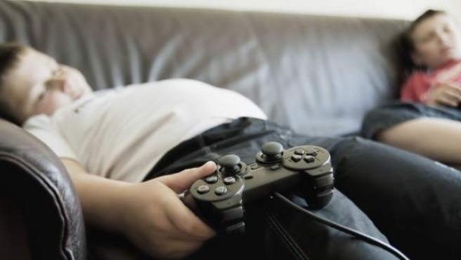 Niño con sobrepeso jugando a la videoconsola.