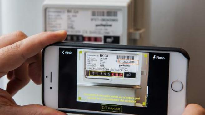 Un cliente realiza la lectura del contador del gas de su casa con el móvil.