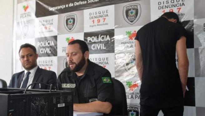 Los comisarios locales Reinaldo Nóbrega (c) y Marcos Paulo Vilela (i) hablan en rueda de prensa en la ciudad de João Pessoa con el arrestado Marvin Henriques Correia (d) de espaldas.