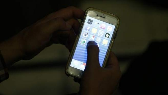 Imagen de archivo de una persona manejando un app en un smartphone.