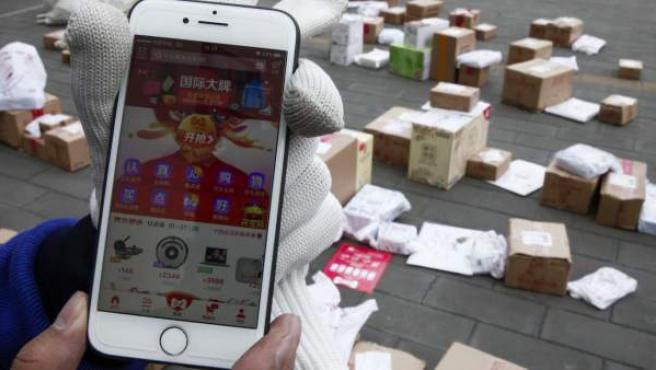 Un repartidor muestra unos paquetes a entregar durante el Día del Soltero, en Pekín.