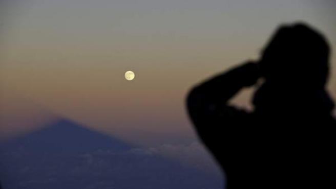 Un hombre contempla como la sombra del volcán Teide, en la isla de Tenerife, se alinea con la superluna.