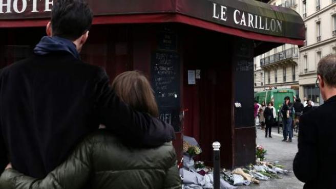 Dos personas se abrazan junto al café Le Carillon, escenario de los atentados de París del 13 de noviembre de 2015.