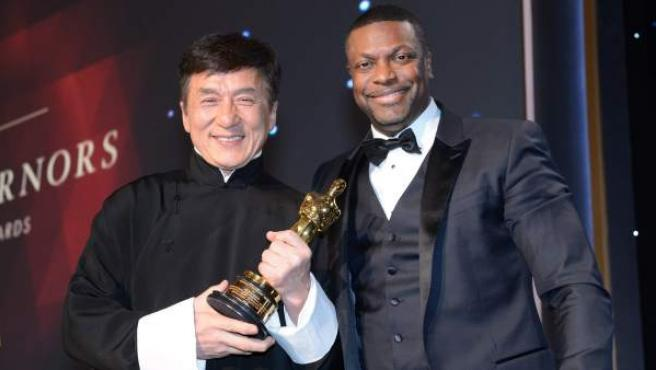 Jackie Chan sostiene su Óscar honorífico junto al actor Chris Tucker.