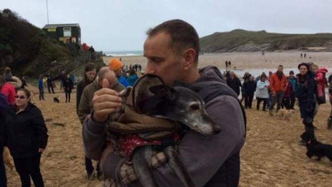 Walnut en brazos de su propietario y rodeado de aquellos que se presentaron para acompañarlos en su último paseo por la playa.