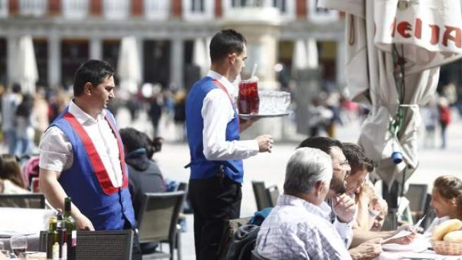 Camareros y turistas en una terraza de la Plaza Mayor de Madrid.
