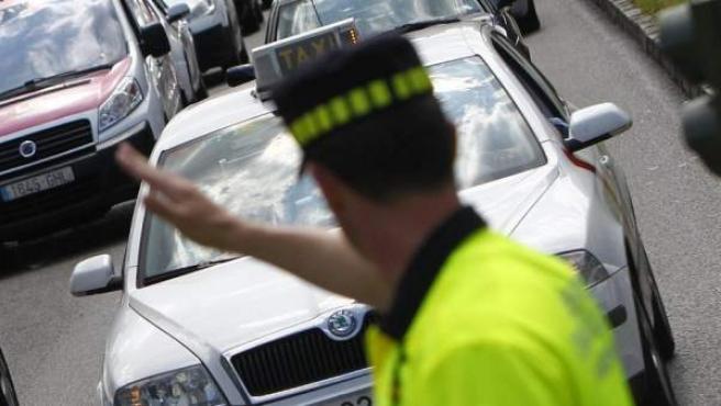 Un agente de Movilidad regula el intenso tráfico en el cruce de la calle Alcalá con Cibeles, en Madrid.