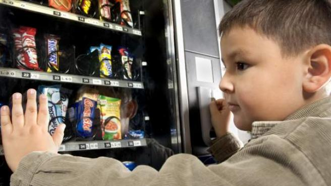 Un niño observa una máquina de chocolatinas.
