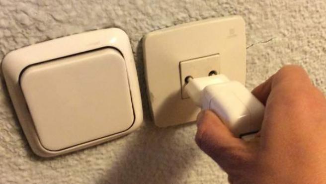 Una persona enchufa un aparato al suministro eléctrico.