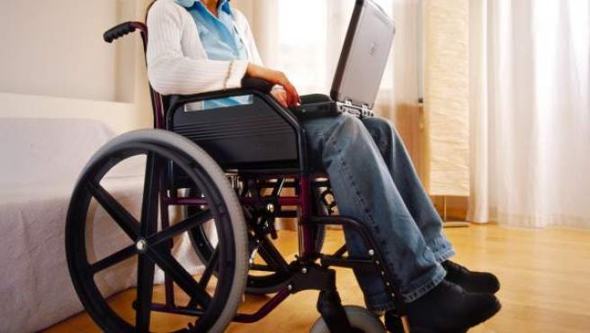 Una persona con discapacidad trabaja con su ordenador portátil.