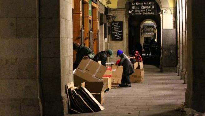 Un grupo de personas sin hogar se prepara para dormir en los soportales de la Plaza Mayor.