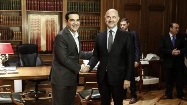 El primer ministro griego, Alexis Tsipras (i), saluda al comisario europeo de Asuntos Económicos, Pierre Moscovici (d), durante su encuentro en Atenas, Grecia.