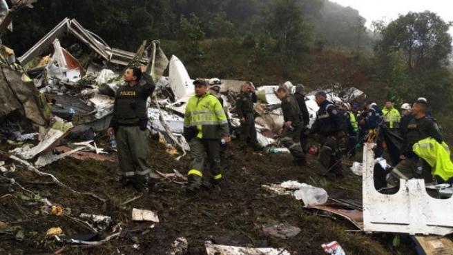 Varios miembros de los servicios de emergencia y agentes de la policía colombiana trabajan entre los restos del avión siniestrado.