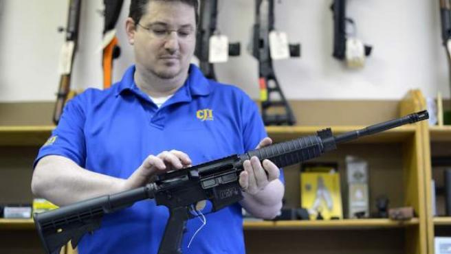 Un propietario de una armería sostiene un rifle semiautomático de asalto MP15 de la firma Smith & Wesson en su negocio en Tucker (Georgia, EE UU)