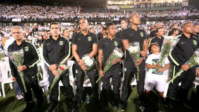 Jugadores del Atlético Nacional de Medellín con flores y de negro, rinden tributo al Chapecoense la noche en que debería haberse jugado la final.
