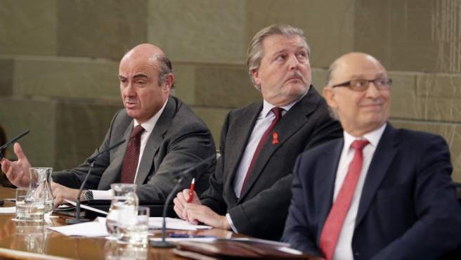 Íñigo Méndez de Vigo (c), junto a Luis de Guindos (i), y Cristóbal Montoro (d), durante la rueda de prensa posterior a la reunión del Consejo de Ministros.