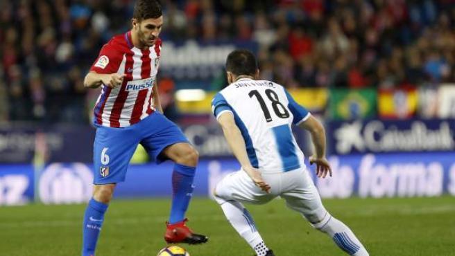 El centrocampista del Atlético de Madrid, Jorge 'Koke' Resurrección (i) controla el balón junto al centrocampista Javi Fuego (d) del Espanyol.