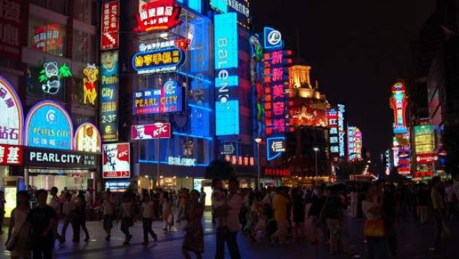 Una calle céntrica de Shangai iluminada por la noche.