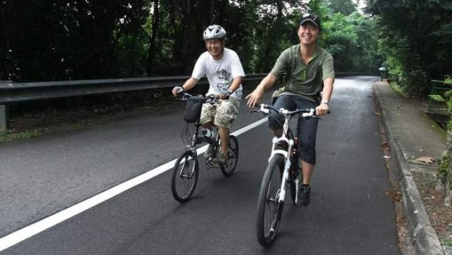 Dos hombres pasean en bicicleta.