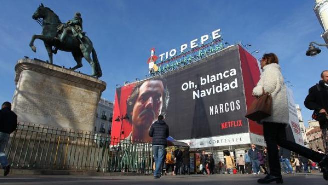 """Cartel publicitario en la Puerta del Sol de Madrid de la serie Narcos de Netflix, con una imagen del actor Wagner Moura que da vida a Pablo Escobar y el lema """"Oh, blanca Navidad"""", cuya retirada ha pedido la ministra de Exteriores de Colombia, María Ángela Holguín."""