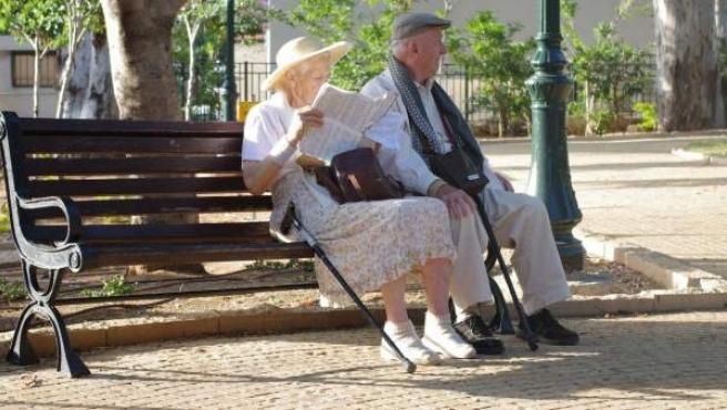 Dos ancianos descansan en un banco de un paseo.