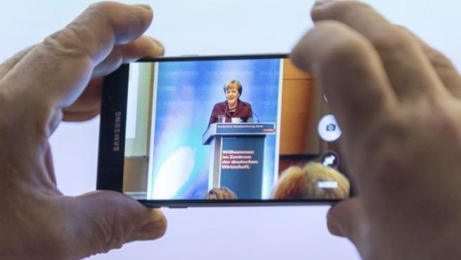 La canciller alemana, Angela Merkel, en la pantalla de un móvil durante el foro de la Confederación de Artesanía Especializada de Alemania (ZDH) en Münster.