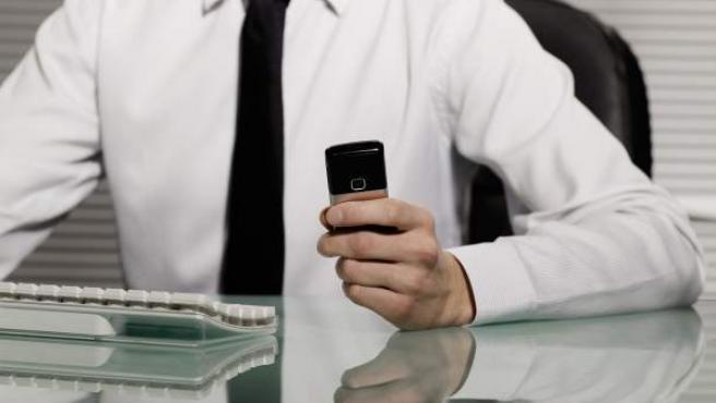 Un hombre trabaja ante el ordenador consultando su teléfono el móvil.