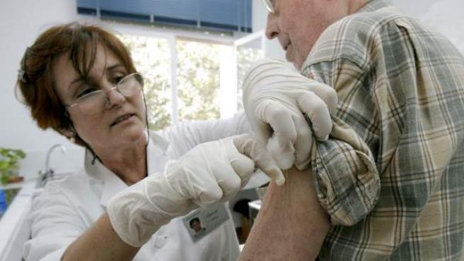 Imagen de archivo de una enfermera poniéndole una inyección a un anciano .