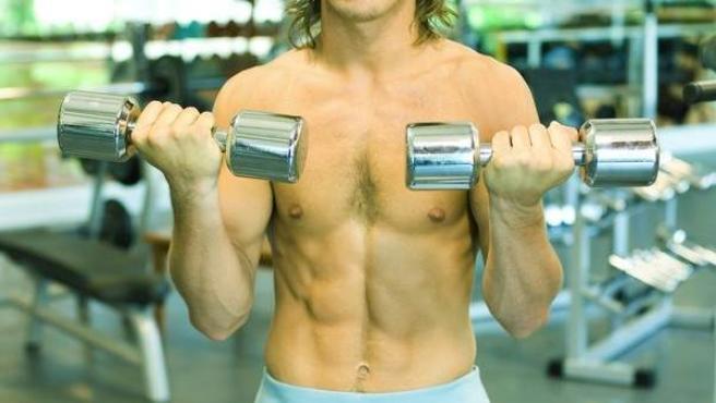 Imagen de un hombre haciendo pesas en un gimnasio.