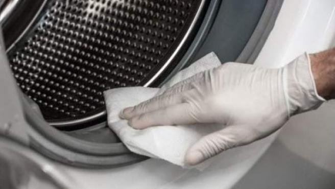 Una persona limpiando el moho de una lavadora.
