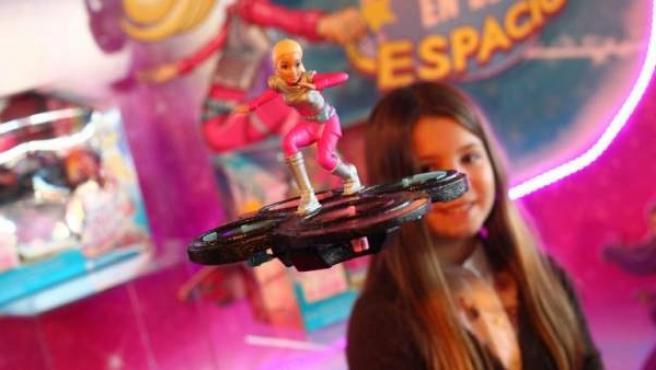 Una niña jugando con una Barbie que vuela sobre un dron.