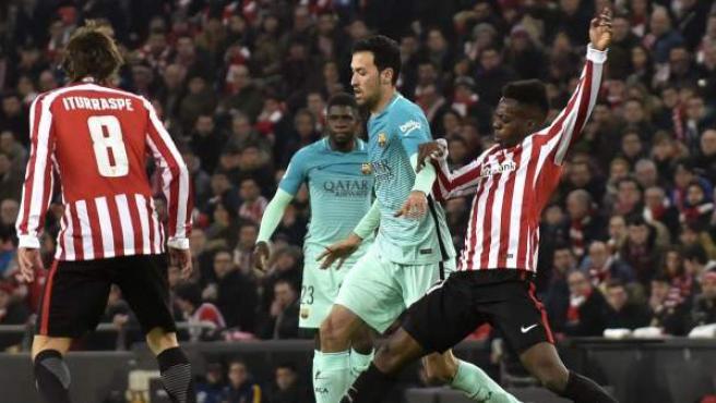 El delantero del Athletic Club de Bilbao Iñaki Williams (d) disputa un balón con el centrocampista del FC Barcelona Sergio Busquets (c), durante el partido de ida de octavos de final de la Copa del Rey.