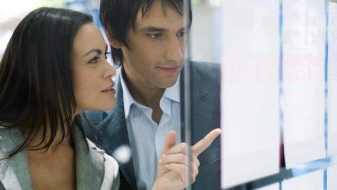 Una pareja mirando las viviendas que oferta una agencia inmobiliaria.